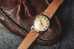 Vintage wristwatch with luxury italian leather strap and brown trendy oxford shoes. Classic timepiece mechanical watch, Men fashion and accessories.