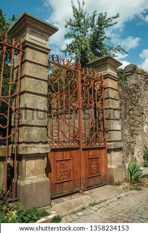 Vintage wrought iron gate covered by rust, in front of old mansion facade with stone decoration at Covilha. Known as the town of wool and snow, stands at Estrela ridge proximity in eastern Portugal. #1358234153