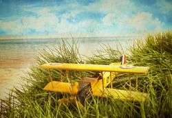 Vintage yellow toy plane in tall grass at the beach with aged vintage look