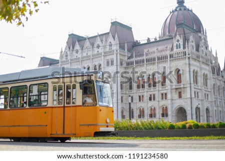 Vintage yellow tram with famous parliament in Budapest city, Hungary in a summer day