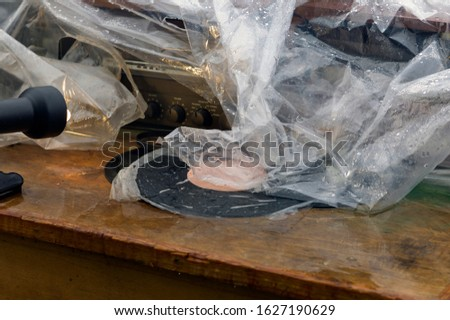Vinyl discs and musical equipment abandoned under rain and partly covered with foil