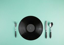 Vinyl record and cutlery set. Music lover with good taste creative concept. Abstract turquoise pastel background with copy space.