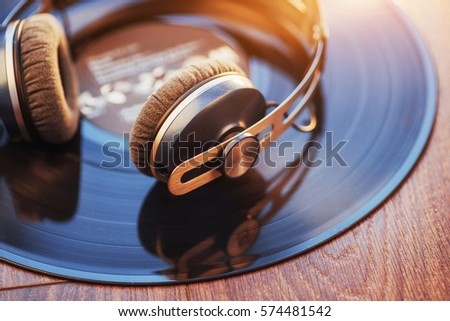 vinyl record and headphone over wooden table. #574481542