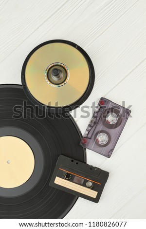 Vinyl record, compact discs and cassettes. Vinyl plate, DVD or CD disks and cassette tapes on wooden background, top view. Vintage musical devices.