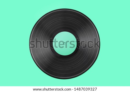 Vinyl record on a colored background. Old vintage vinyl record isolated on turquoise  background