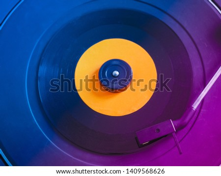 Vinyl record on a turntable record player, single 45rpm disc, pink and blue light #1409568626