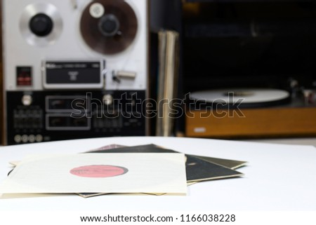 Vinyl record with copy space in front of a collection albums dummy titles. Reel Tape Recorder #1166038228