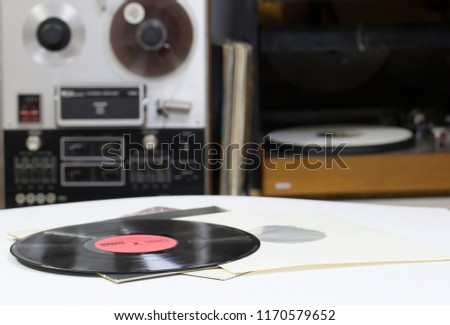Vinyl record with copy space in front of a collection albums dummy titles. Reel Tape Recorder #1170579652