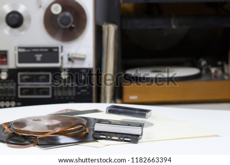Vinyl record with copy space in front of a collection albums dummy titles. Reel Tape Recorder. Audio cassetes tap. #1182663394