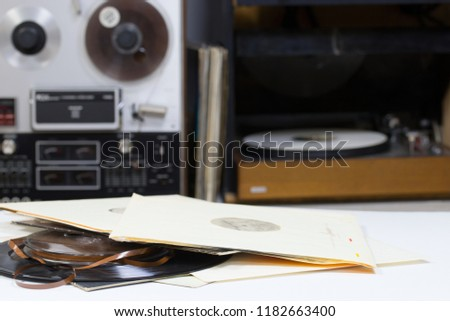 Vinyl record with copy space in front of a collection albums dummy titles. Reel Tape Recorder #1182663400