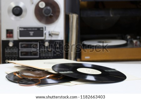 Vinyl record with copy space in front of a collection albums dummy titles. Reel Tape Recorder #1182663403