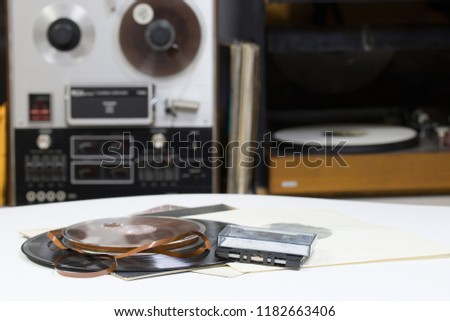 Vinyl record with copy space in front of a collection albums dummy titles. Reel Tape Recorder. Audio cassetes tap. #1182663406