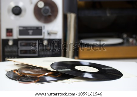 Vinyl record with copy space in front of a collection albums dummy titles, vintage process #1059161546