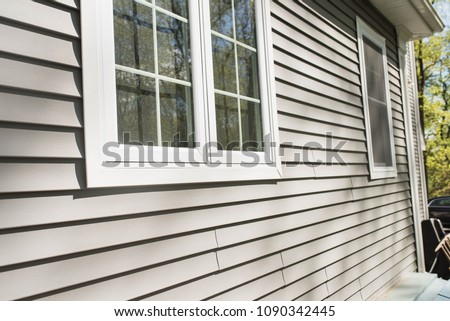 vinyl siding on house with window frames - Shutterstock ID 1090342445