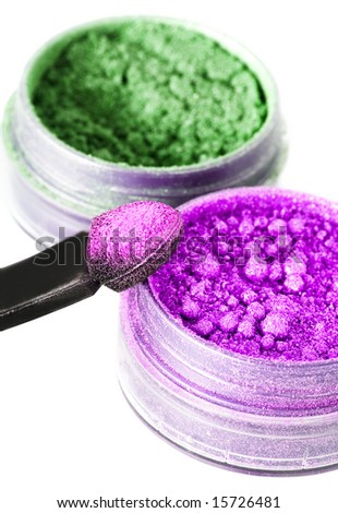 violet and green make-up eyeshadows and cosmetic brush