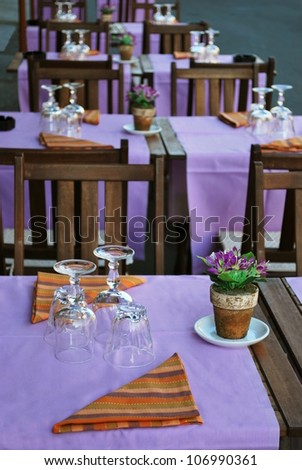 Violet and orange table setting in outdoor restaurant, Milan, Italy