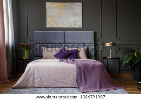 Violet blanket on the bed in pastel bedroom interior with grey poster on grey wall with molding #1086791987