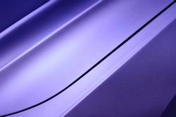 Violet car bodywork detail, part of hood and fender of sport sedan, steel gradient line pattern, automobile industry, horizontal selective focus