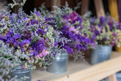 Violet dried flowers in blue tin watering flower pot on wooden table background.
