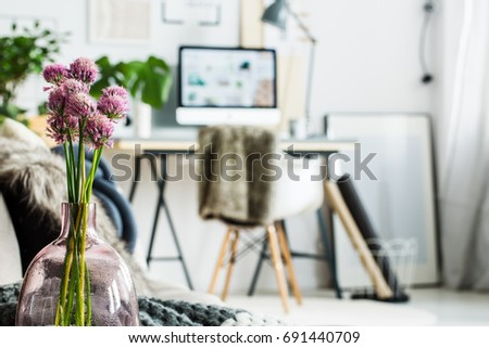 Violet flowers in glass vase in simple office room with picture on floor #691440709