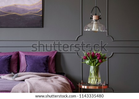 Violet tulips on copper table next to bed in feminine bedroom interior with lamp and poster