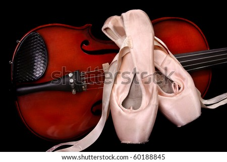 Violin and ballet shoes on black.