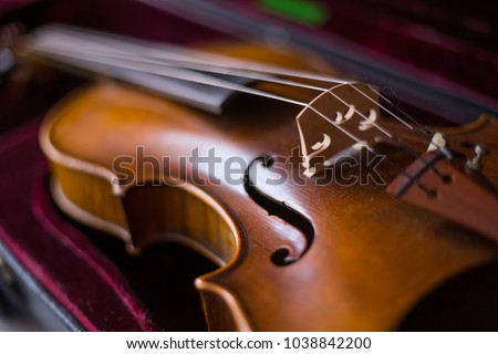 Violin and bow in dark red case. Close up #1038842200
