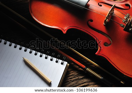 Violin and notebook on wooden table