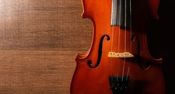 Violin, details of a beautiful violin on wooden surface and black background, low key selective focus portrait.