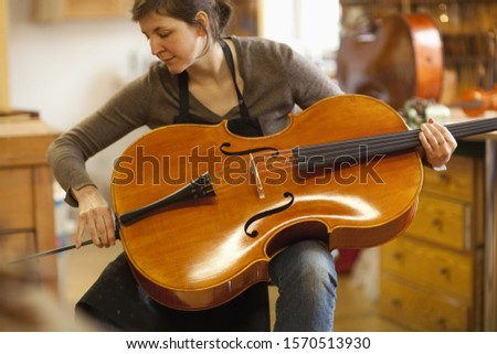 Violin maker checking cello in workshop