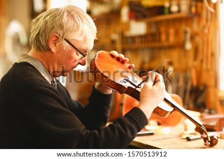 Violin maker checking violin in workshop