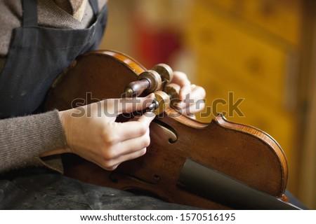 Violin maker restoring a violin