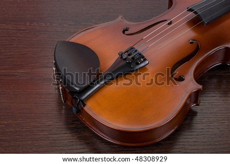 violin on a brown wooden background closeup