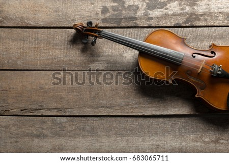 Violin on a wooden textured table Stock fotó ©