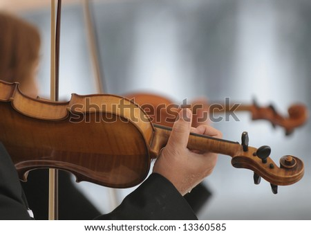 Violin players on defocussed background.