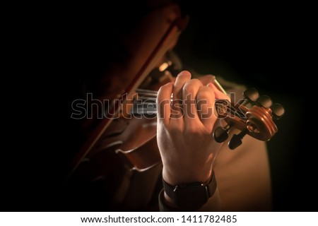 Violin playing musician in closeup in front of black background. Fiddler in action. Foto d'archivio ©