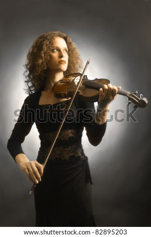 Violin playing violinist musician symphony. Artistic portrait of beautiful woman fiddler music performer