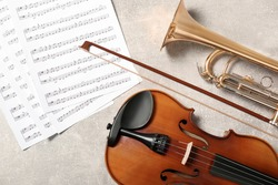 Violin, trumpet and note sheets on light grey background, flat lay. Musical instruments