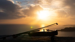 Violin with bow by the sea at sunset