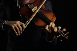 Violinist player hands close up shot  in black isolated background