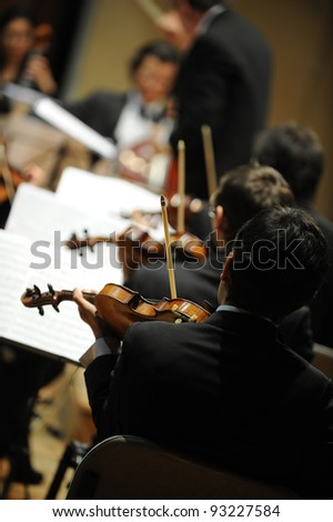 violinists during a classical concert music, music conductor on background