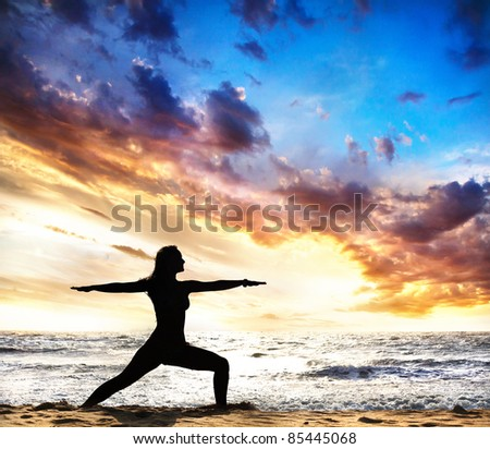 virabhadrasana II warrior pose by beautiful Woman silhouette on the sand beach and ocean nearby at sunset background in India, Goa