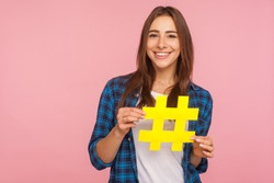 Viral blog post. Happy pretty smiling girl in checkered shirt holding yellow hashtag symbol, making important topic popular, setting trends on Internet. indoor studio shot isolated on pink background