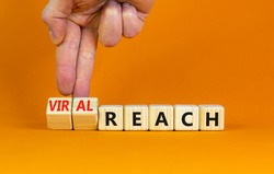 Viral reach symbol. Businessman turns wooden cubes and changes words 'reach' to 'viral reach'. Beautiful orange table, orange background, copy space. Business, viral reach concept.