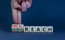 Viral reach symbol. Businessman turns wooden cubes and changes words 'reach' to 'viral reach'. Beautiful grey table, grey background, copy space. Business, viral reach concept.