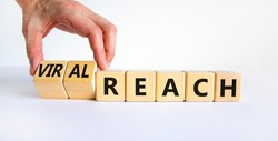 Viral reach symbol. Businessman turns wooden cubes and changes words 'reach' to 'viral reach'. Beautiful white table, white background, copy space. Business, viral reach concept.