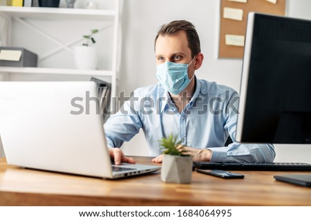 Viral threat, seasonal viral diseases. A man works in the office in a medical mask, protecting office workers from viruses