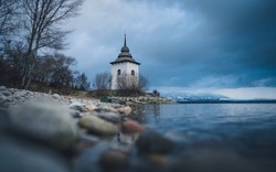 Virgin Mary Church by Liptovska Mara Lake with Rocks in Foreground at Twilight in Slovakia. Waterscape at reservoir Liptovska Mara in Slovakia
