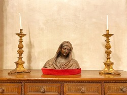 Virgin Mary sculpture, statue on a wooden table surrounded by two long golden candles. Copyspace for text
