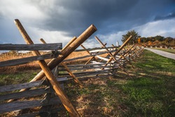 Virginia worm or split rail fence constructed of wood located at Oak Ridge on the field where Battle of Gettysburg took place during the Civil War, with the Eternal Light Peace Monument in background